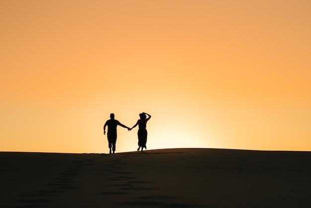 Silhouetten eines glücklichen jungen paares mann und frau