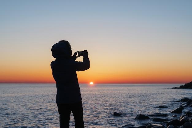 Silhouetten eines mädchens, das fotos des sonnenuntergangs auf dem meer auf einem smartphone macht