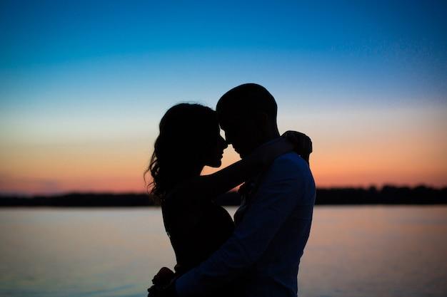 Silhouetten eines paares in liebesromantik bei sonnenuntergang.