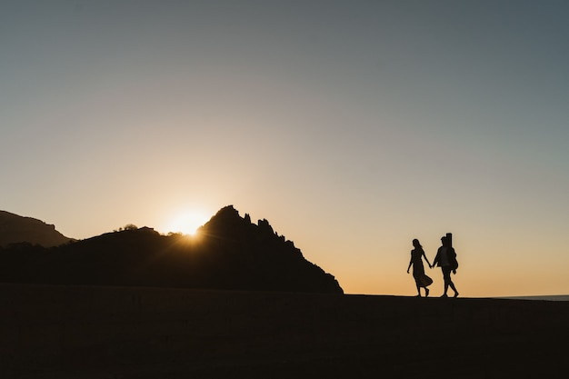 Silhouetten eines verliebten paares. romantische fotografie in der nähe der berge. ein junges paar geht am meer spazieren.
