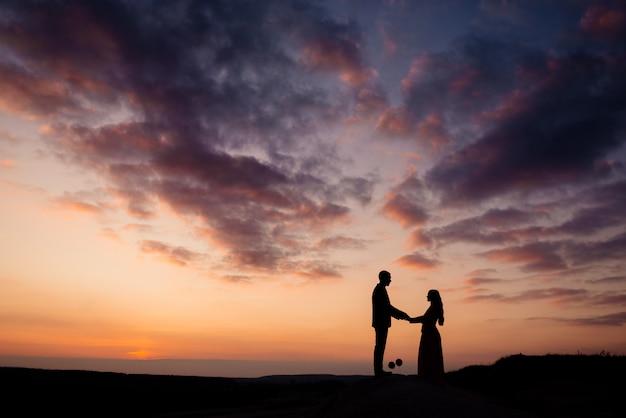 Silhouetten von braut und bräutigam, die jungvermählten sehen sich händchen haltend an. hochzeitsfotografie-konzept. speicherplatz kopieren