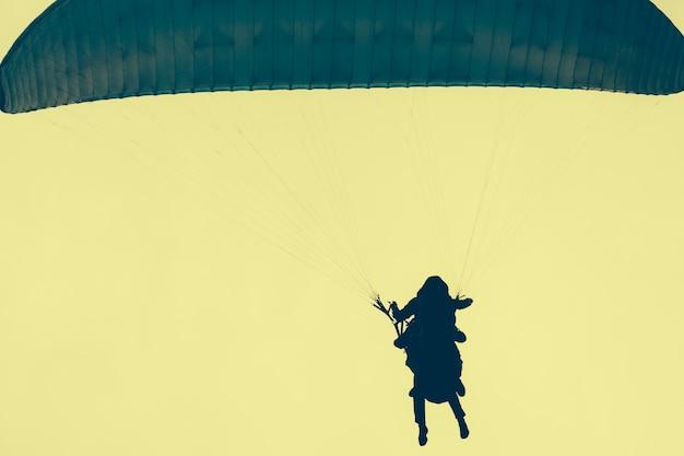 Silhouetten von fallschirmspringern in einem gelben himmel