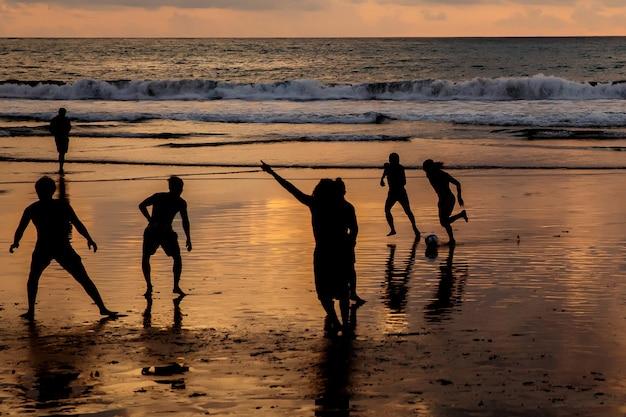 Silhouetten von jungs, die bei sonnenuntergang am meeresstrand fußball spielen.