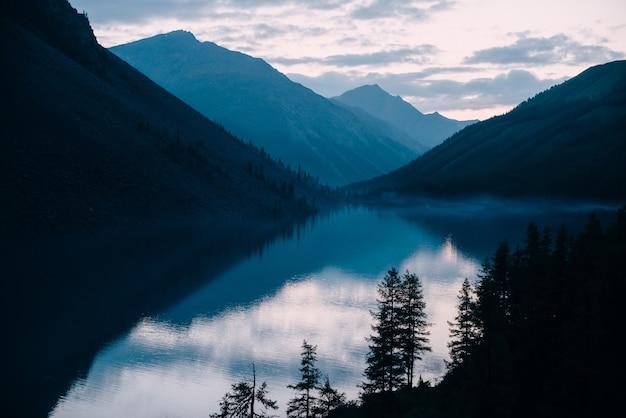 Silhouetten von lärchen auf hintergrund der silhouetten des hochlandsees und der berge.