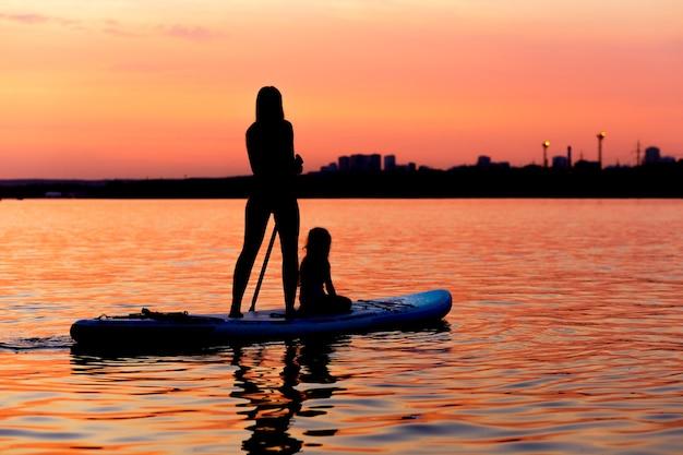 Silhouetten von mädchen und kindern, die bei sonnenuntergang auf paddle board paddeln