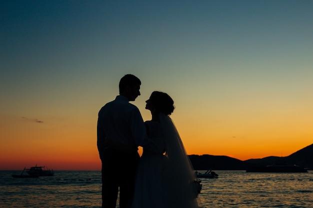 Silhouetten von paaren nahe sveti stefan insel in montenegro