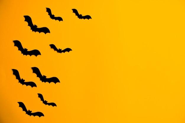 Silhouetten von schwarzen fledermäusen aus papier auf orangefarbenem hintergrund. halloween-grußkarte