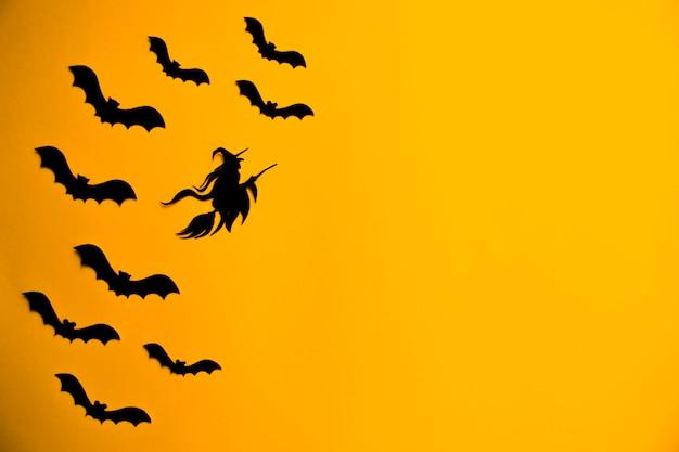 Silhouetten von schwarzen fledermäusen und hexe auf besenstiel.