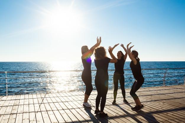 Silhouetten von sportlichen frauen, die bei sonnenaufgang highfive in der nähe des meeres geben