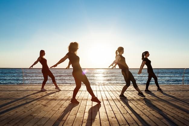 Silhouetten von sportlichen frauen, die nahe meer bei sonnenaufgang tanzen