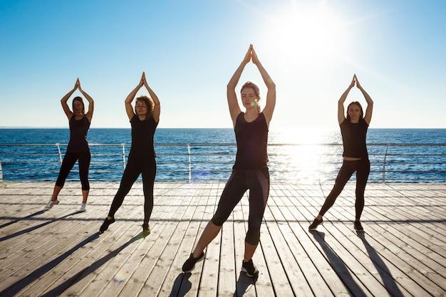 Silhouetten von sportlichen frauen, die zumba nahe meer bei sonnenaufgang tanzen