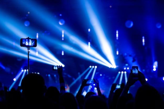 Silhouetten von zuschauermassen bei einem konzert mit smartphones in der hand. die szene wird von scheinwerfern wunderschön beleuchtet.