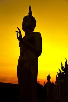 Silhouettieren sie bild von buddha auf goldenem sonnenunterganghimmel