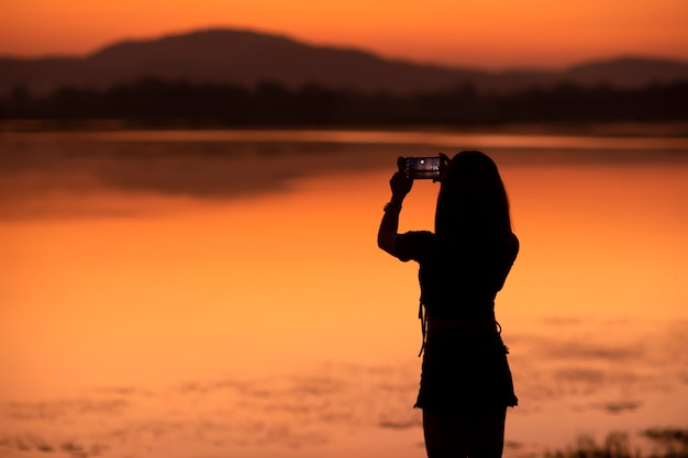 Silhouettieren sie das asiatische mädchen, das ein foto durch ihr mobile an den touristenattraktionen im sonnenuntergang, sakonnakhon, thailand macht.