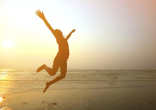 Silhouettieren sie das junge mädchen, das mit den händen oben auf dem strand bei dem sonnenuntergang, bewegungsunschärfe springt