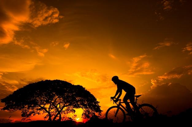 Silhouettieren sie den mann, der bergauf mit fahrrad bei sonnenuntergang mit orange himmel in der landschaft fährt.
