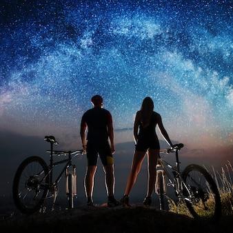 Silhouettieren sie den paarradfahrer, der nächtlichen himmel mit vielen sternen genießt. biker mit mountainbikes auf dem hügel in der nacht
