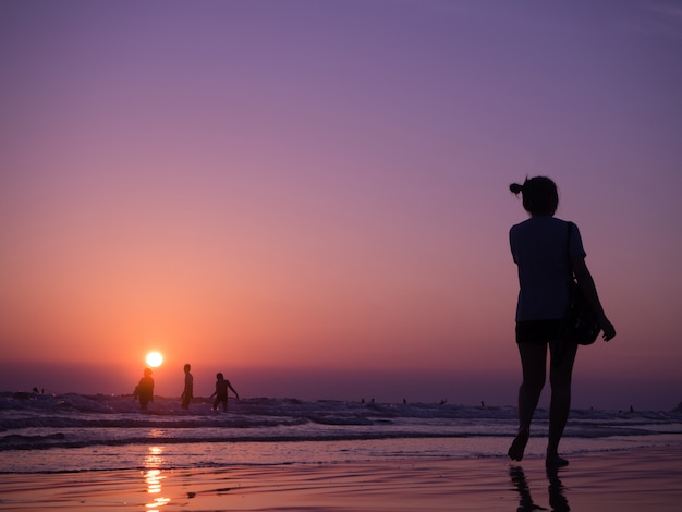 Silhouettieren sie den schatten der jungen asiatischen frau, die auf strand mit sonnenuntergang geht. konzept des urlaubsstrandes.