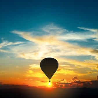 Silhouettieren sie die bunten heißluftballone, die über gebirgsland fliegen