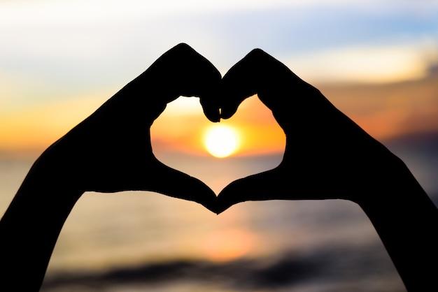 Silhouettieren sie die frauenhände, um herzform auf sonnenunterganghintergrund zu sein. liebe, valentinstag c