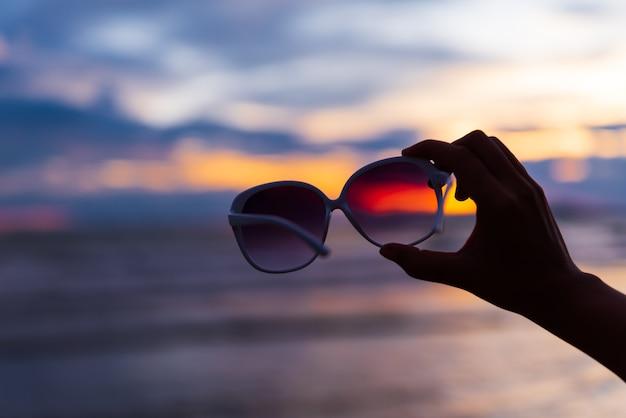 Silhouettieren sie die frauenhand, die sonnenbrille über meer während des sonnenuntergangs hält