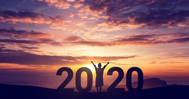 Silhouettieren sie die junge frau der freiheit, die auf dem hügel und 2020 jahren beim feiern des neuen jahres genießt, kopieren sie raum.
