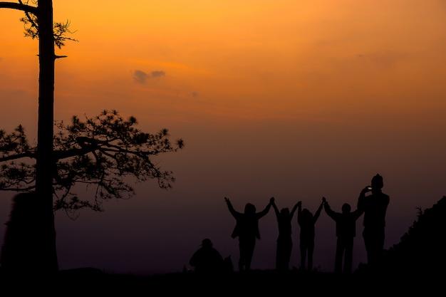 Silhouettieren sie die stehende gruppe von personen und zeigen sie ihre hand im sunse