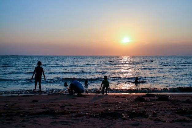 Silhouettieren sie familie und haustier am strand- und seesandsonnenuntergang