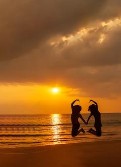 Silhouettieren sie foto des liebessymbols von einem paar auf dem strand bei sonnenuntergang