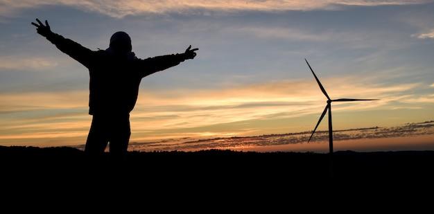 Silhouettieren sie glücklichen mann mit den händen hoch und windkraftanlage in der sonnenaufgangzeit.