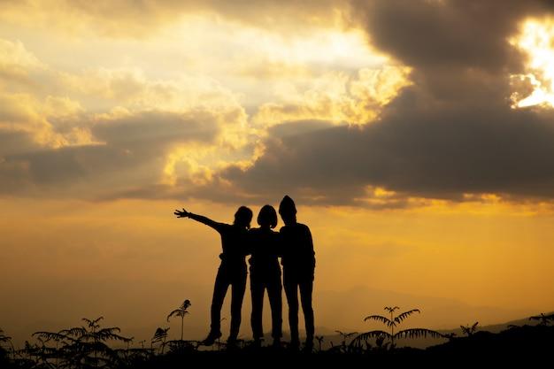 Silhouettieren sie, gruppe des glücklichen mädchens spielend auf hügel, sonnenuntergang