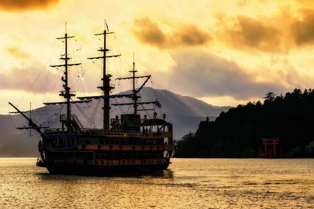 Silhouettieren sie piratenschiff ein torii tor am see ashi