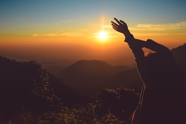 Silhouettieren sie steigende hände der frau auf berg am morgen mit weinleselicht, nordthailand