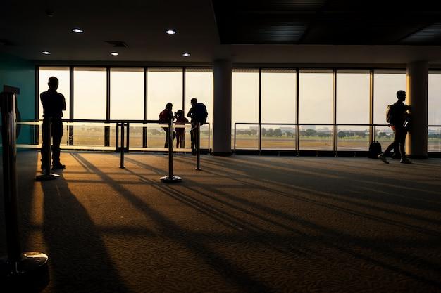 Silhouettieren sie touristen am flughafenabfertigungsgebäude bei sonnenaufgang