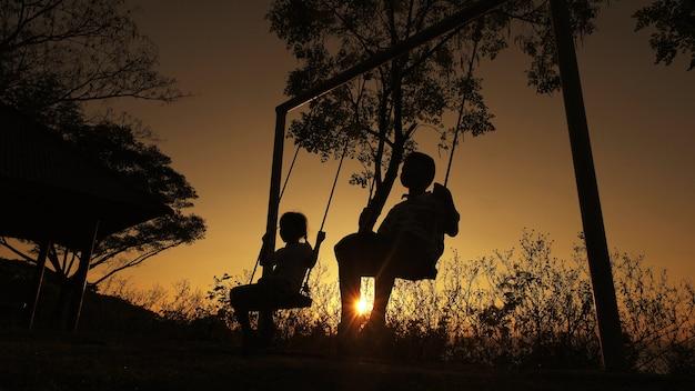 Silhouettierter kinderjunge und -mädchen, die den schönen sonnigen tag spielt hintergrund genießt