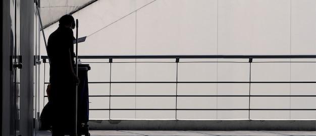 Silhoutte-bilder von reinigungsdienstmitarbeitern, die rund um die terrasse im gebäude für hygienische arbeiten arbeiten