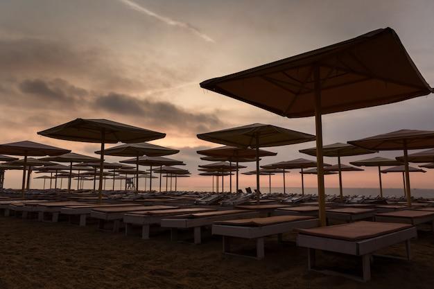Silhuettes der strandruhesessel und -regenschirme auf einem leeren strand am abend