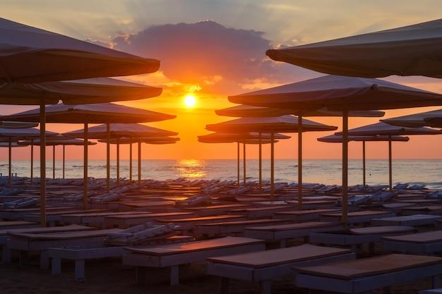Silhuettes von strandruhesesseln und -regenschirmen auf einem einsamen strand am abend auf einem sonnenunterganghintergrund