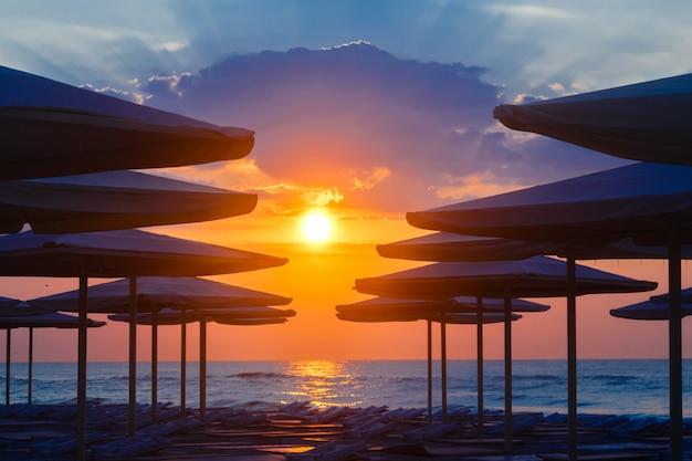 Silhuettes von strandruhesesseln und -regenschirmen auf leerem strand am abend auf einem sonnenunterganghintergrund