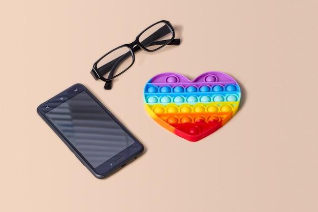Silikon-regenbogen-herz-antistress-pop it auf einem hintergrund mit brille und einem telefon.