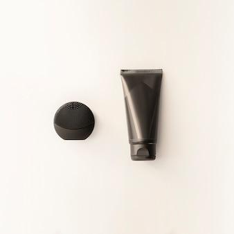Silikon schwarz gesichtsbürste und creme schwarzes rohr isoliert. modell für männliches zubehör schönheitsblogkonzept männerkosmetikebenenlage für das einbrennen. set schwarze körperpflegeprodukte