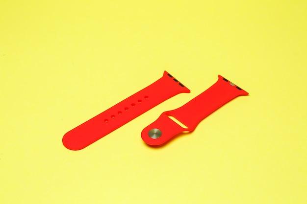 Silikonarmband für smartwatch rote farbe auf gelbem hintergrund
