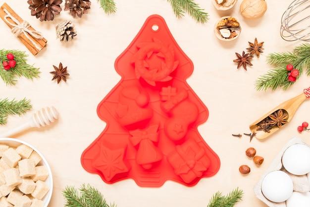 Silikonform und zutaten für die herstellung von weihnachtsplätzchen auf hölzernem hintergrund
