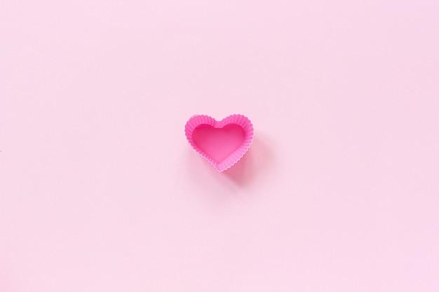 Silikonherz formte formteller für das backen der kleinen kuchen auf rosa papierhintergrund.