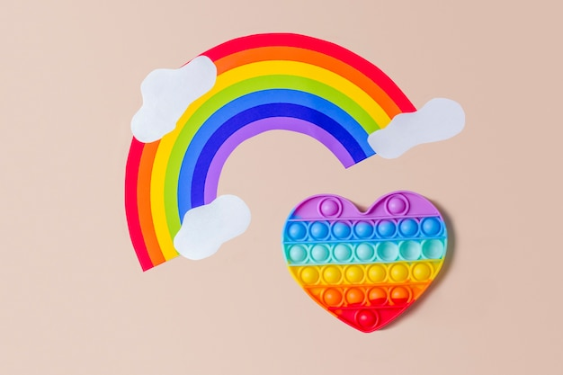 Silikonregenbogenherz auf beigem hintergrund mit regenbogen und wolken.
