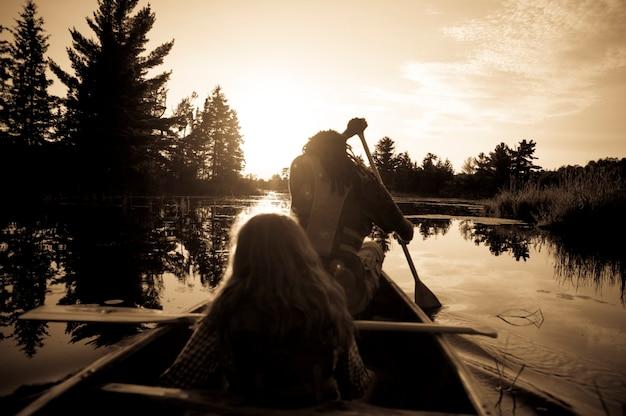 Sillhouette von den leuten, die ein kanu am see des holzes, ontario rudern