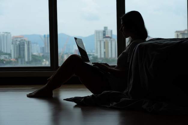 Siluet mädchen, das an einem laptop arbeitet und kaffee trinkt, auf dem boden nahe dem bett durch das panoramafenster mit einem schönen blick vom hohen boden sitzend sitzt. stilvolles modernes interieur. ein gemütlicher arbeitsplatz