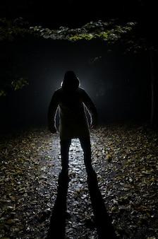 Siluette des mannes im wald in der nacht