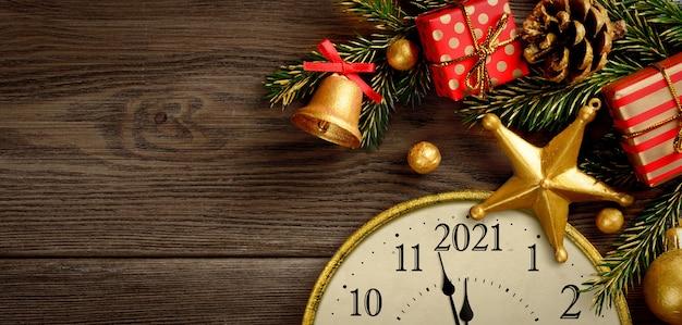 Silvester 2021. retro-stil uhr mit weihnachtsschmuck und geschenken auf braunem holzhintergrund. letzte momente vor weihnachten oder neujahr