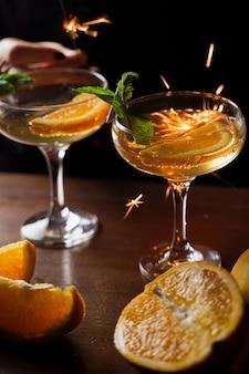 Silvester 2022 mit wunderkerzen-feuerwerk und cocktails feiern. minze mit orangenscheibe in einem cocktailglas gefüllt mit alkoholcocktails.